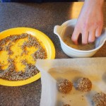 Rolling the thumbprint cookies in egg white then nuts