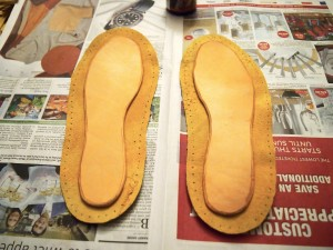 Gluing the leather insoles into the moose hide moccasins
