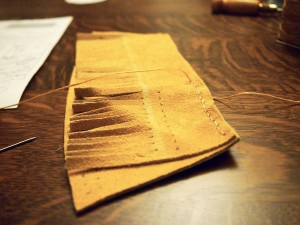 Sewing the fringe to the heel piece on the moose hide moccasins