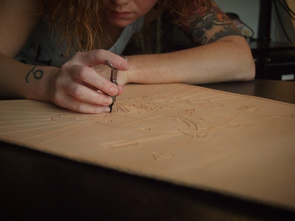 Using the swivel knife to cut out the art in the leather quiver