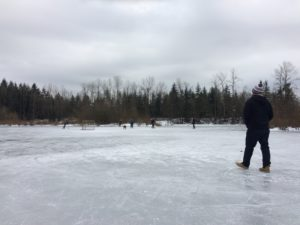 Walking on the frozen pond while the locals play hockey